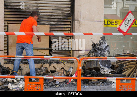 An insurance comapny expert looks at a building damaged by fire, Lyon, France - Stock Photo