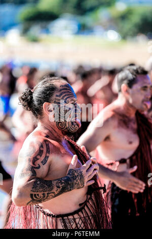 Fearsome Maori warriors with facial moko tattoos perform Kapa Haka on Waitangi day at Waitangi, New Zealand - Stock Photo