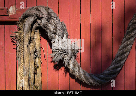 Old grey unwinding rope hanging on red wooden wall - Stock Photo