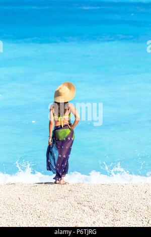 Woman with straw hat on famous Myrtos beach. Kefalonia, Greek Islands, Greece (MR) - Stock Photo