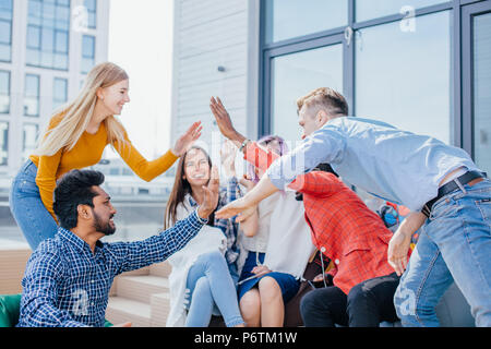 Young friends giving high five after making a good deal and earning a lot of money on marketing targeting investigation - Stock Photo