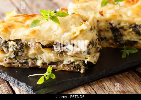 Italian lasagna with chicken, wild mushrooms, mozzarella and parmesan cheese and bechamel sauce close-up on a slate plate. horizontal - Stock Photo