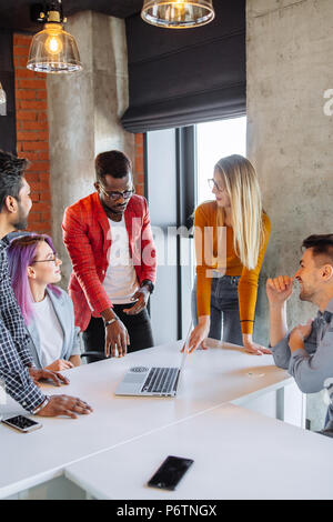 Diverse multiethnic group of young businesspeople in office boardroom gathering together around white table, discussing their business strategy and sh - Stock Photo