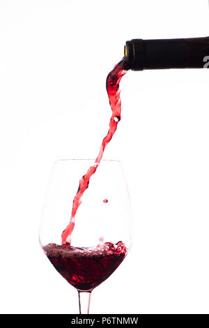 Red wine pouring in a wine glass, on a white background - Stock Photo