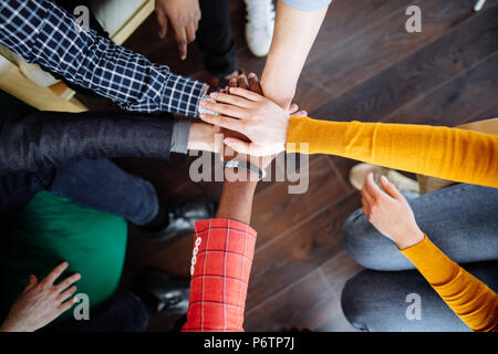 Cropped view of multiracial male and female hands or arms wearing casual colorful long sleeve shirts giving high five together against wooden backgrou - Stock Photo