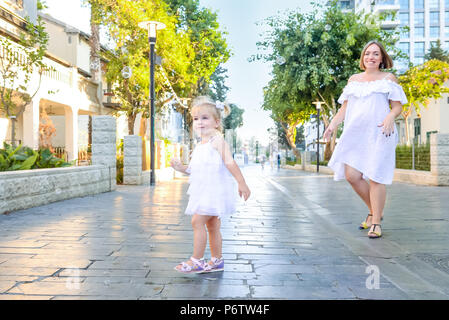Cute little emotional blondy toddler girl in dress with pregnant mother playing, catching soap bubbles during walk in the city park. Active family lei - Stock Photo