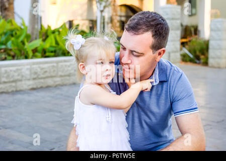 Portrait of cute little blondy toddler girl in white dress hugging her father and telling him something during walk in the city park. Active family le - Stock Photo