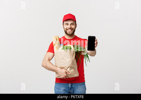 Delivery man holding paper bag with food and showing blank phone screen on white background - Stock Photo