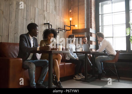 Multiracial millennials enjoying coffee working on gadgets in co - Stock Photo