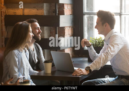 Male architect consulting excited millennial couple in coffee sh - Stock Photo