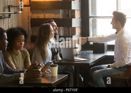 Smiling male broker greeting customers with handshake at cafe me - Stock Photo