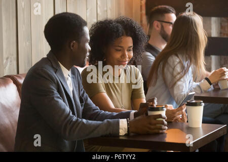 Multiracial people enjoying coffee to go during break in cafe - Stock Photo