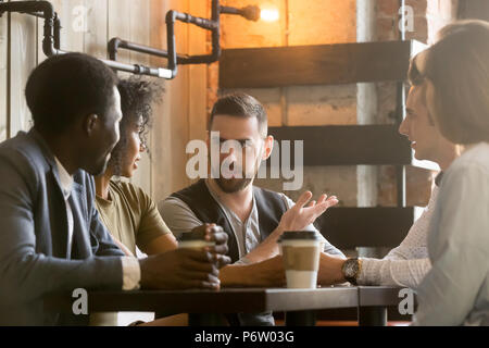 Multiracial colleagues discussing ideas during work break in caf - Stock Photo