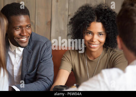 Happy black friends enjoying meeting with colleagues out in cafe - Stock Photo