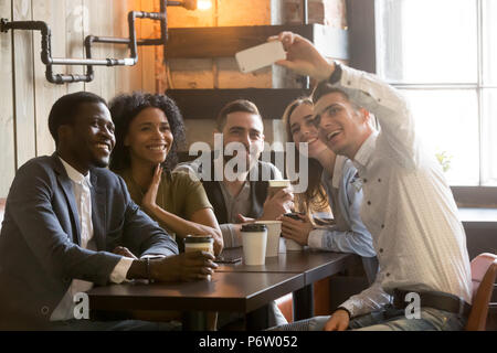 Multiracial friends smiling making selfie in cafe - Stock Photo