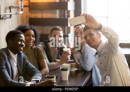Millennial friends having fun making selfie in cafe - Stock Photo
