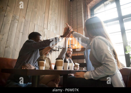 Happy diverse friends giving high five chilling out in cafe - Stock Photo