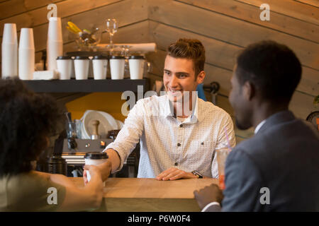 Caucasian barista serving coffee to black girl during date - Stock Photo