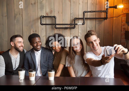 Caucasian man taking group photo with diverse friends in cafe - Stock Photo