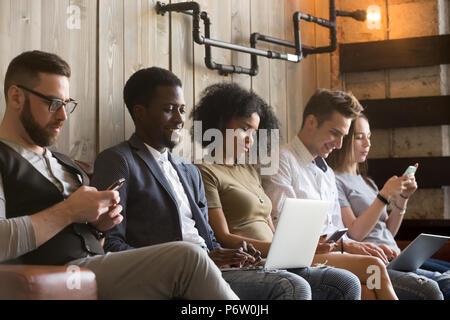 Multiracial millennials sit avoid talking using gadgets - Stock Photo