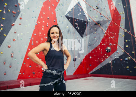 Portrait of happy fit girl with harness on her waist after successful ascent, rise, in climbing club studio over painted artificial rock background. - Stock Photo