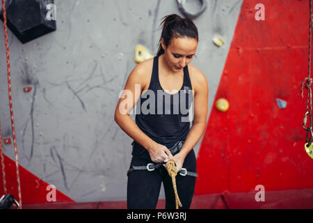 Athletic female climber in safety harness tying rope in eight knot and preparing to climb. Climbing equipment - Stock Photo