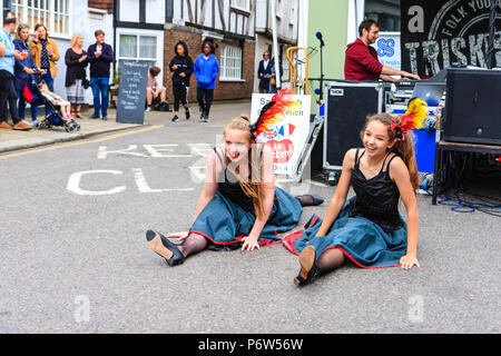 Two young women, teenage girls, performing the Can-Can in a street during a festive event. Stage with musicians behind them. - Stock Photo