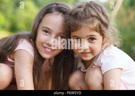 Two Happy little girls  hugging at the  summer park - Stock Photo
