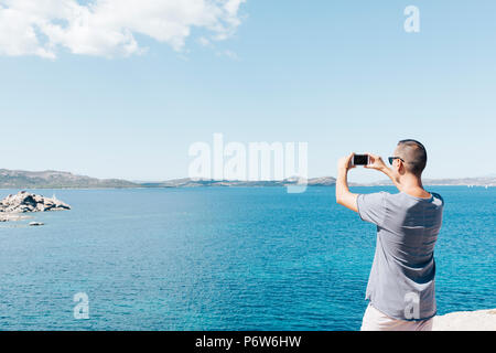 closeup of a young caucasian man seen from behind taking a photo of the sea in the Costa Smeralda, in Sardinia, Italy, with his smartphone, with a bla - Stock Photo