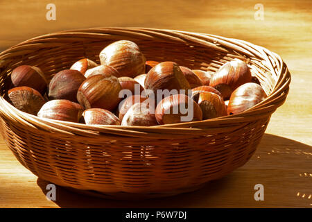 Hazelnuts in a basket on a wooden table - Stock Photo