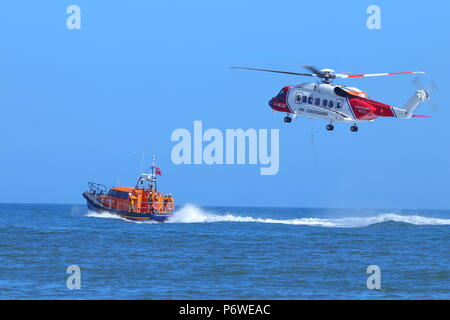 A Sikorsky S-92 putting on a public training exercise with the RNLI Lifeboat of Scarborough during National Armed Forces Day - Stock Photo