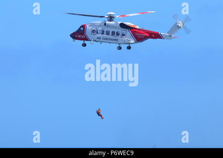 A Sikorsky S-92 putting on a public training exercise with Scarborough RNLI during National Armed Forces Day - Stock Photo