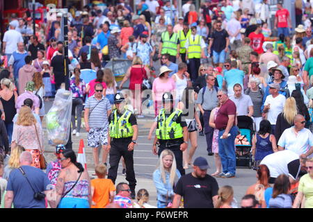 Police Officers on patrol on a packed street on Scarborough seafront, as the National Armed Forces Day event takes place. - Stock Photo