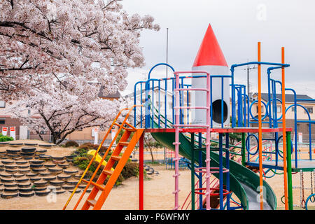 Colorful playground with cherry blossoms on park in Japan - Stock Photo