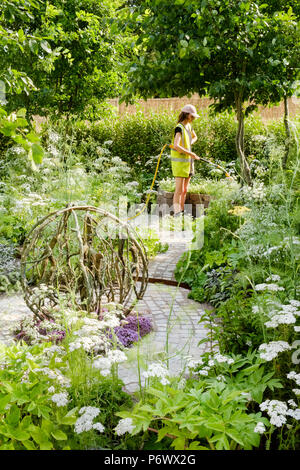 London, UK. 2nd-8th July 2018. RHS Hampton Court Flower Show - The Health and Wellbeing Garden. Early morning watering, the signature of this year's RHS Hampton Court Flower Show, with temperatures reaching around 35deg C. Garden Designer:  Alexandra Noble - Stock Photo