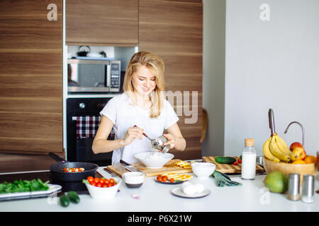 Woman making healthy salad from fresh vegetables, holding plate with tomato cherry and spinach. Frying pan with roasted chicken kebab standing on the  - Stock Photo