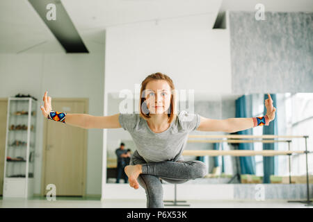 Woman doing balancing exercises during a yoga workout adopting a hand to big toe standing balance pose on one leg with outstretched arms and leg over  - Stock Photo