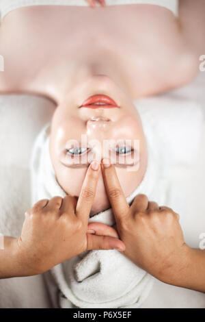 High angle portrait of an attractive woman getting recreation face massage in spa resort - Stock Photo