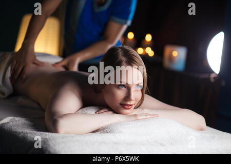 Hands massaging the back, lying on the belly of a woman - Stock Photo