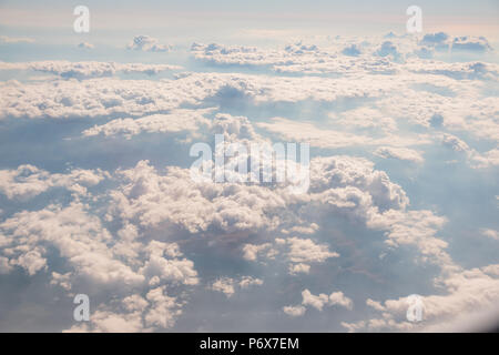 Skyline View above the Clouds from air plane. Go to vacation concept.Sunrise above clouds from airplane window.Panorama sky from altitude in the cumulus and layered stratus clouds. - Stock Photo