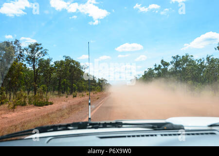 Hazardous driving through flying red dust on the Peninsula Development Road (PDR), Cape York Peninsula, Far North Queensland, FNQ, QLD, Australia - Stock Photo