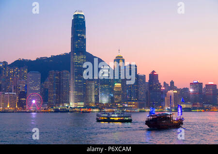 Junk boat in Victoria Harbour at dusk, Hong Kong Island, Hong Kong - Stock Photo