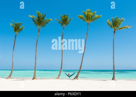 Juanillo Beach (playa Juanillo), Punta Cana, Dominican Republic. Woman relaxing on a hammock on a palm-fringed beach (MR). - Stock Photo