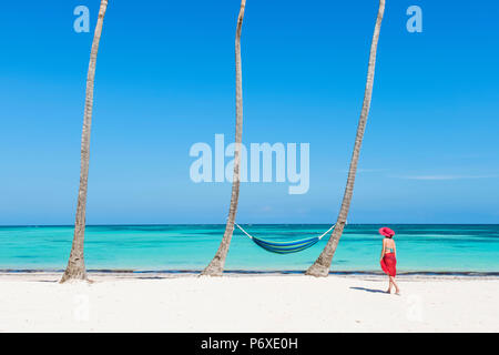 Juanillo Beach (playa Juanillo), Punta Cana, Dominican Republic. Woman walking on a palm-fringed beach (MR). - Stock Photo