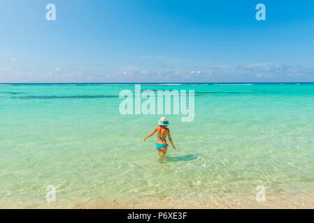 Canto de la Playa, Saona Island, East National Park (Parque Nacional del Este), Dominican Republic, Caribbean Sea. Woman relaxing on the clear waters of the Caribbean Sea (MR). - Stock Photo