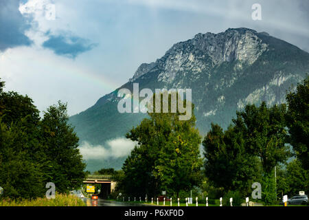 Rainbow over a mountain in the Bavarian countryside - Stock Photo