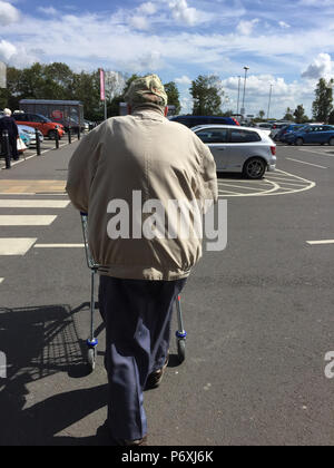 Rear view of elderly man pushing shopping trolley in supermarket car park - Stock Photo