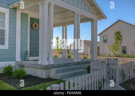 Blue door and white pillars on home entry - Stock Photo