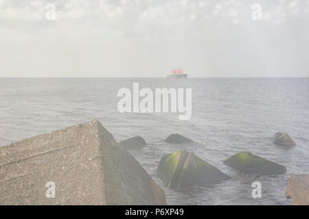 A merchant ship walks along the horizon line of the Baltic Sea against the backdrop of storms on the shore - Stock Photo