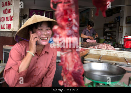 Woman butcher selling meat and on the phone with conical hat in Can Tho, Vietnam - Stock Photo